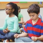 Two students meditating during morning meeting in the classroom